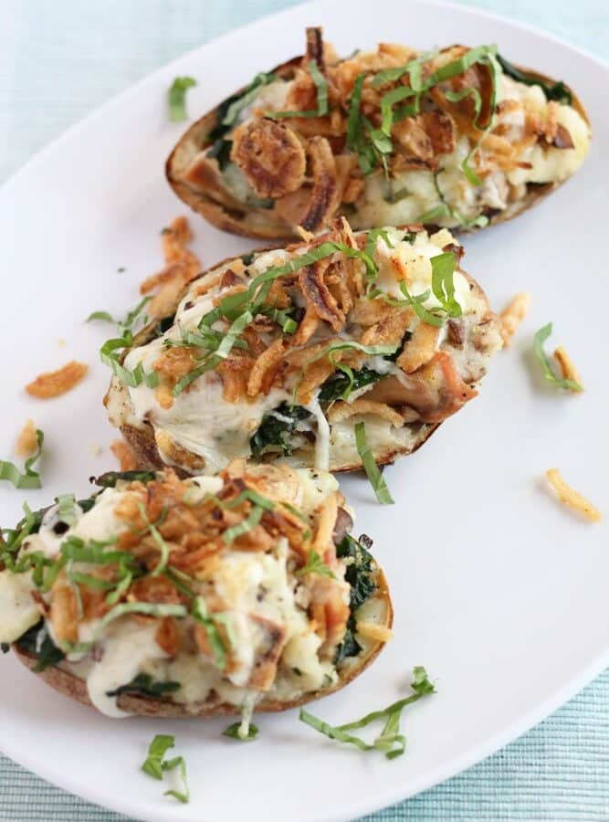 three chicken florentine stuffed baked potatoes on a white platter