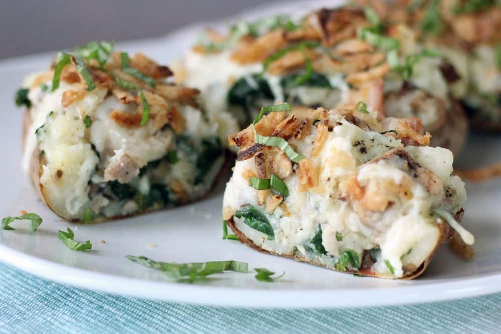 a chicken florentine stuffed baked potato sliced in half horizontally to show the filling