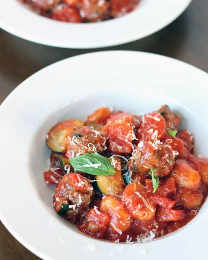 gnocchi with meatballs in a red sauce garnished with grated Parmesan cheese and basil leaves in white bowls