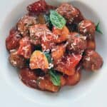a mixture of potato gnocchi, sliced zucchini and small meatballs covered in red sauce in a round white bowl