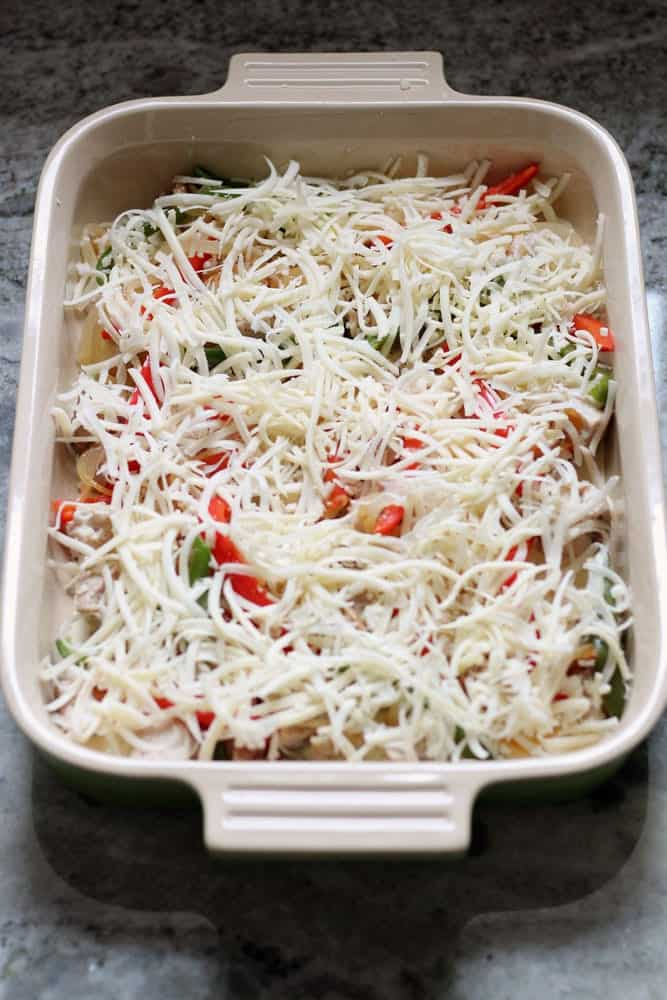 a casserole with red and green peppers covered with shredded white cheese in a rectangular baking dish