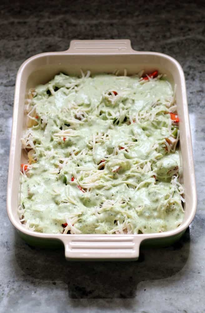 an unbaked casserole covered in a light green colored sauce and topped with shredded white cheese