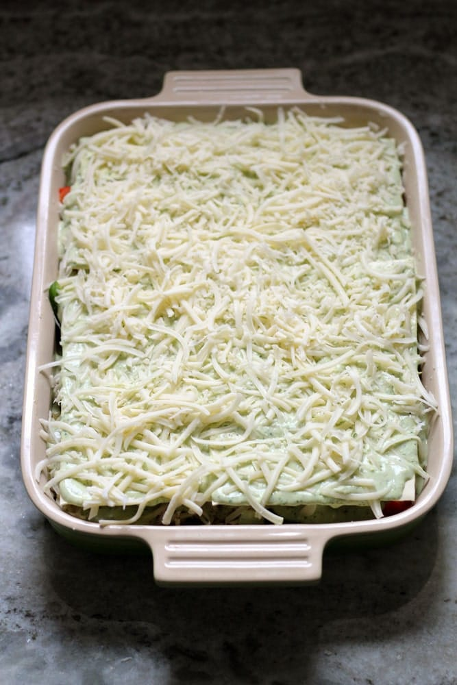 an unbaked lasagna covered with white shredded cheese in a rectangular casserole dish