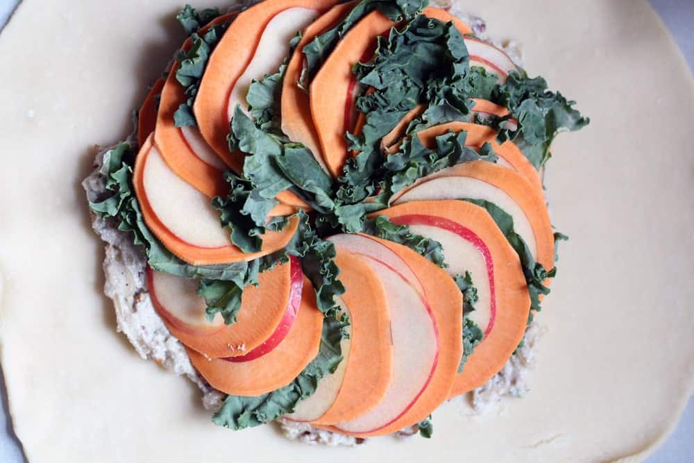thin slices of apple and sweet potato fanned between leaves of green kale