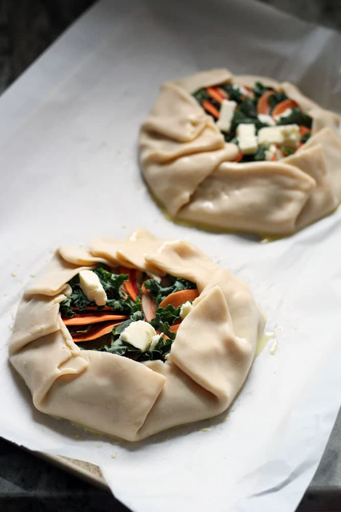 two unbaked galette pastries filled with orange and green vegetables on a baking sheet