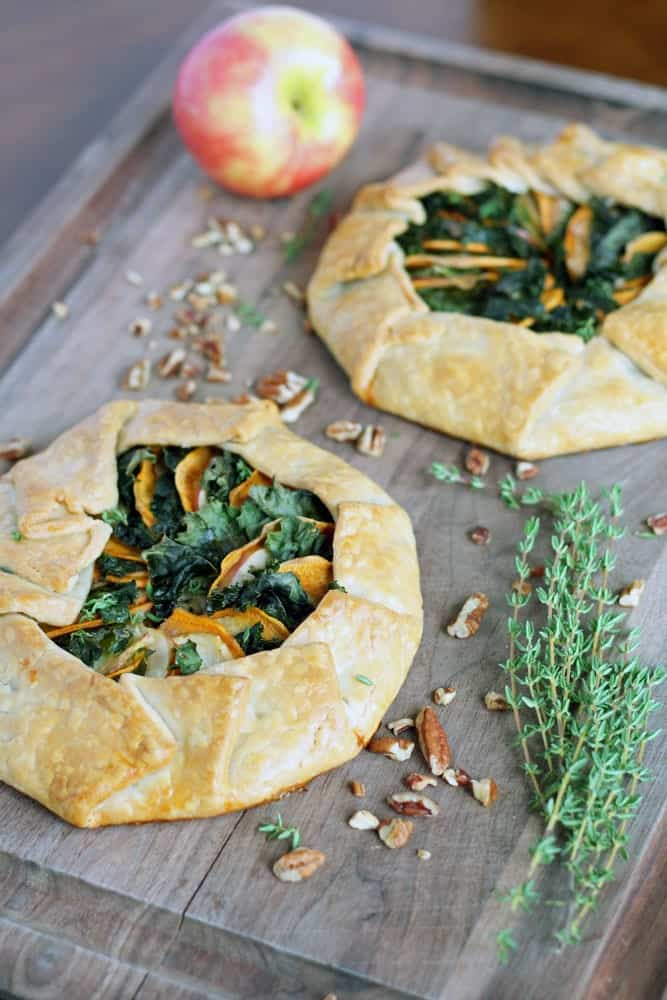 two round baked pastries filled with leafy greens and thinly sliced sweet potato on a cutting board