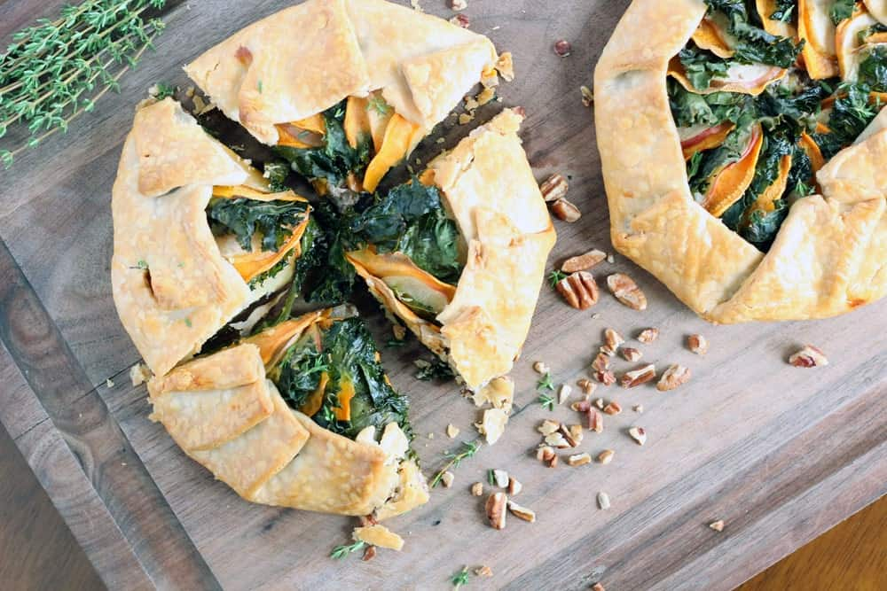 a sweet potato apple and kale galette cut into four wedges aside an uncut galette of the same variety