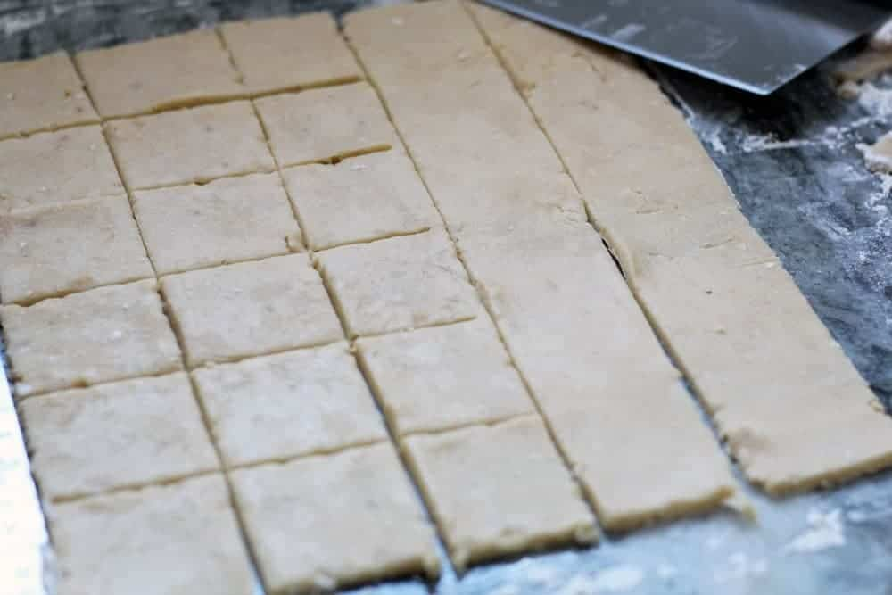 a sheet of cookie dough being scored into squares