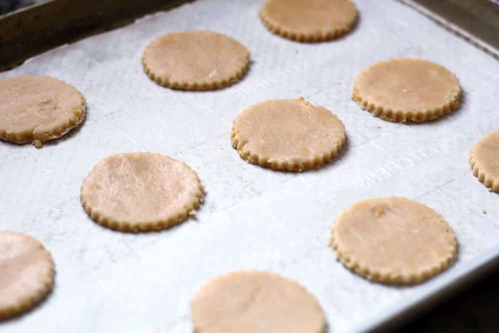 unbaked circles of cookie dough on a cookie sheet lined with white parchment paper