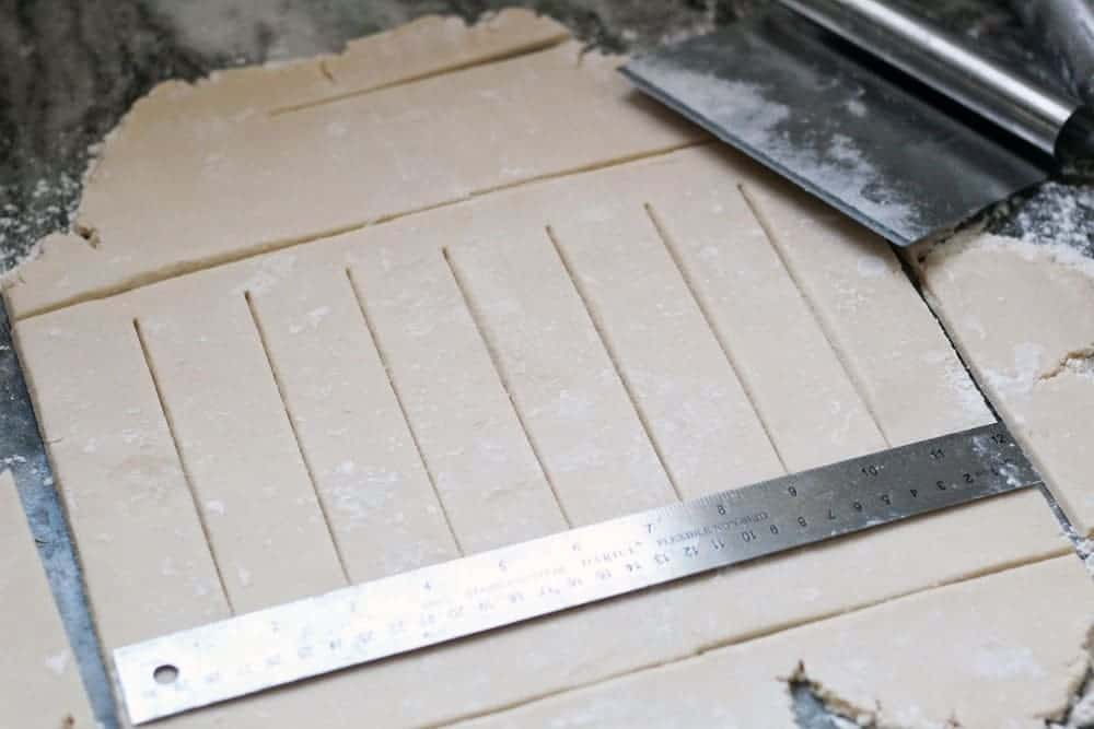 a sheet of pastry dough scored into strips measured by a metal ruler laying on the dough