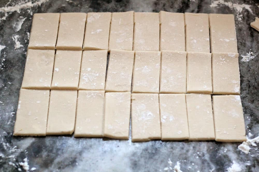 cut rectangles of cookie pastry dough on a floured dark marbled counter top