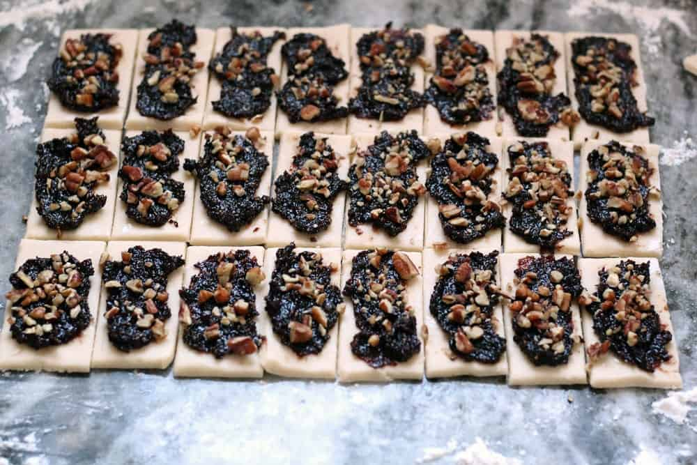 three rows of pastry dough rectangles spread with fig puree and sprinkled with chopped pecans