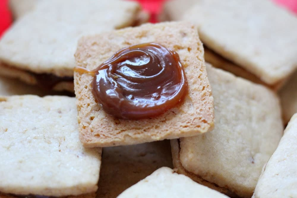 a square shortbread cookie spread with a swirl of light brown colored caramel