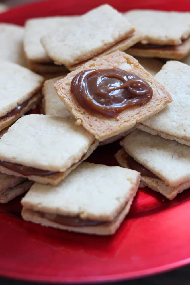shortbread sandwich cookies filled with caramel on a round red plate