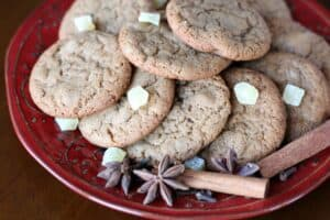 a red plate stacked with brown cookies garnished with candied ginger, star anise, and cinnamon sticks