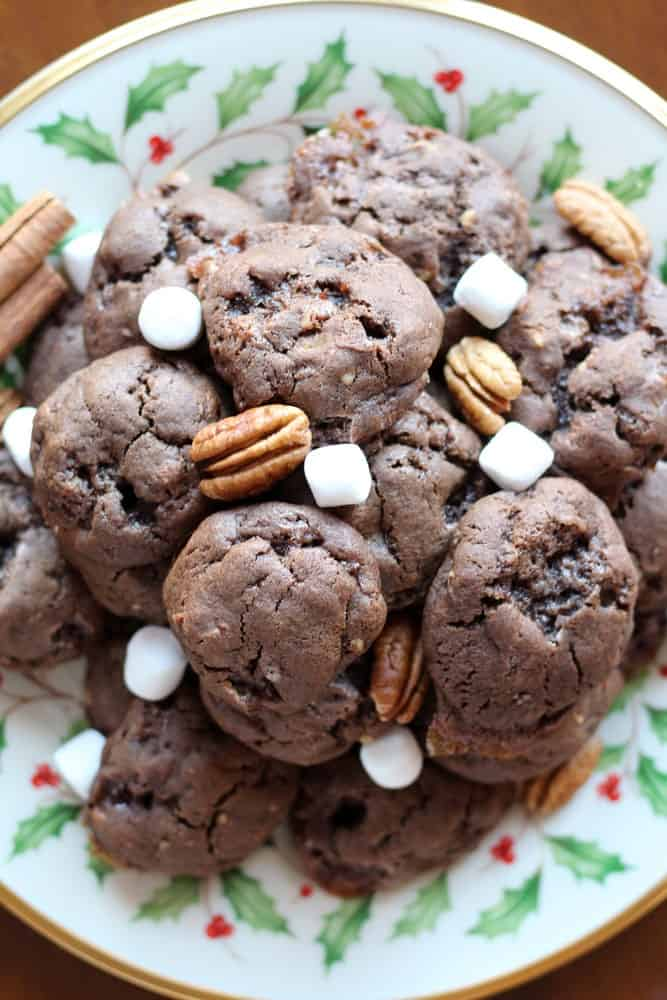 chocolate cookies on a christmas patterned plate garnished with marshmallows and pecans