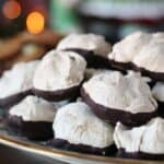a holly & ivy patterned gold rimmed plate piled with meringue cookies dipped in chocolate