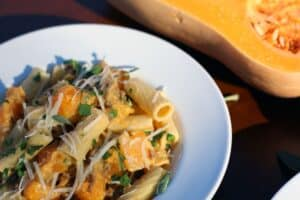 a bowl filled with a mixture of rigatoni pasta, ground sausage, and butternut squash