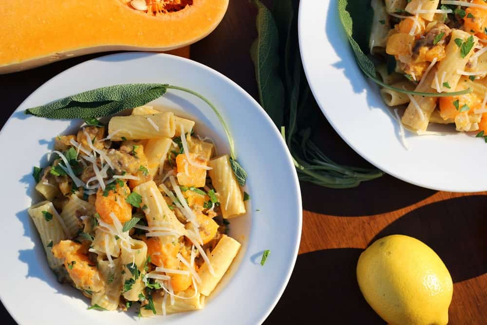 sausage and butternut squash rigatoni served in white bowls and topped with white shredded cheese and chopped green herbs