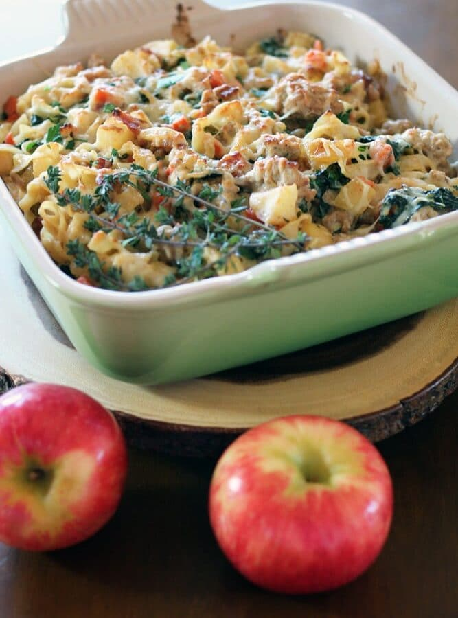 a square baking dish filled with a mixture of diced apple, pork, and spinach topped with melted cheese