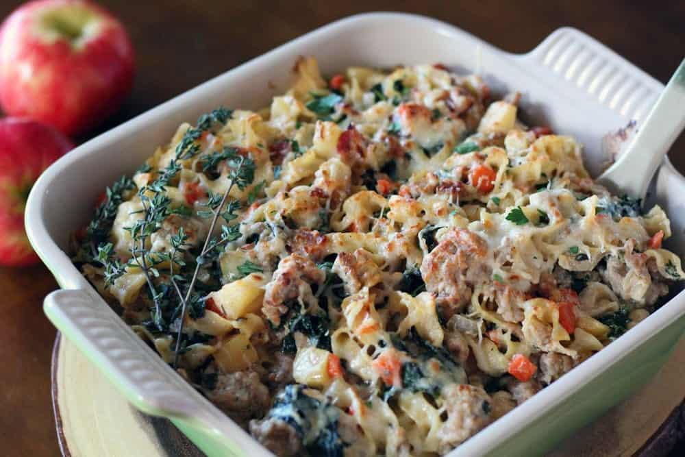 a mixture of pasta with ground meat, bacon, diced apple, and spinach topped with melted cheese in a baking dish