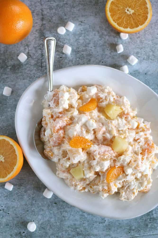 orange and marshmallow ambrosia salad in a white bowl