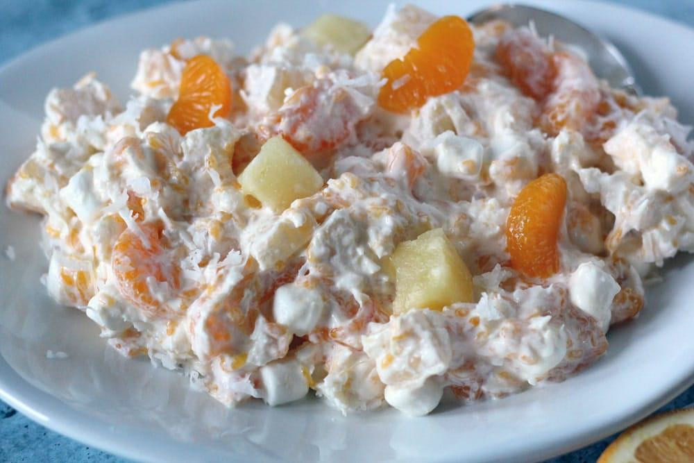 a mixture of mandarin oranges, pineapple chunks, and marshmallows in a creamy coconut sauce