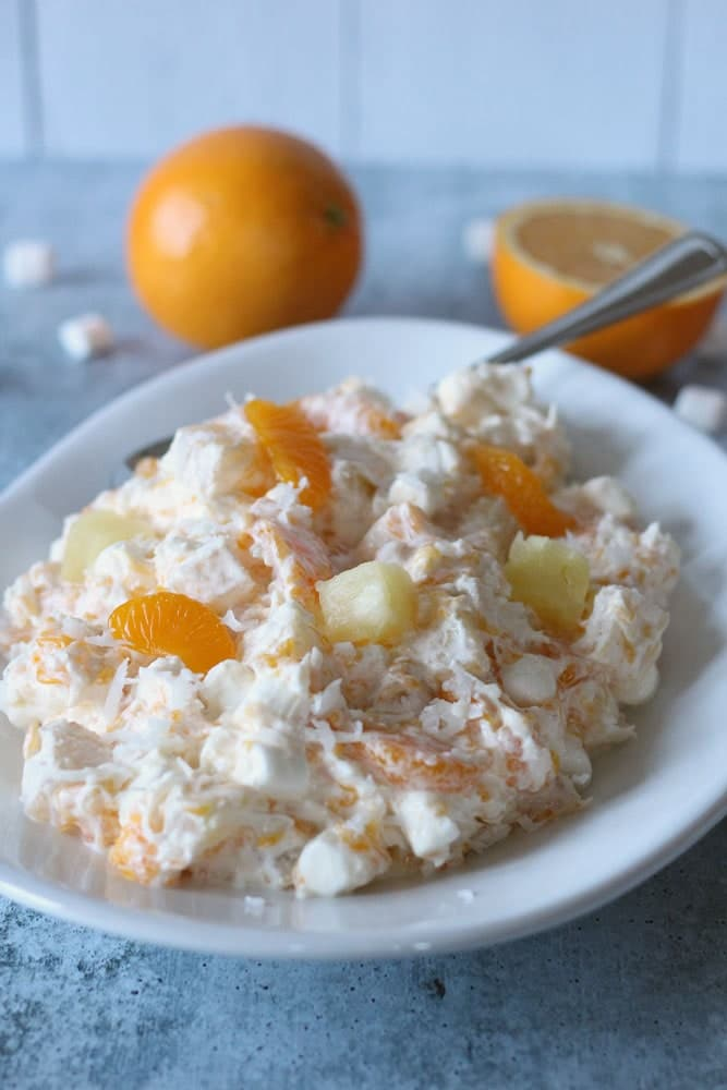 a bowl filled with an orange and white creamy fruit and marshmallow salad