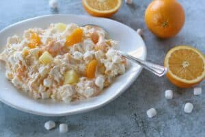 an ambrosia salad of pineapple, oranges and marshmallows in a white bowl