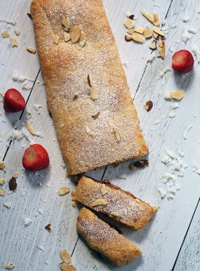 a rectangle-shaped strudel garnished with sliced, chopped almonds on a whitewashed wood surface