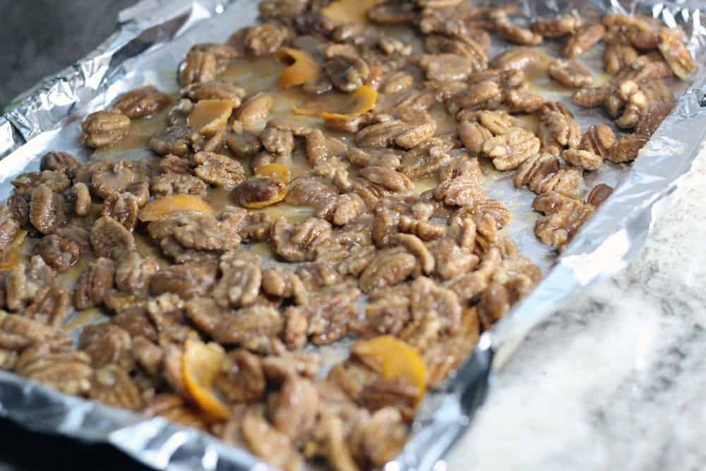 glazed and sugared pecans spread onto a foil lined baking sheet