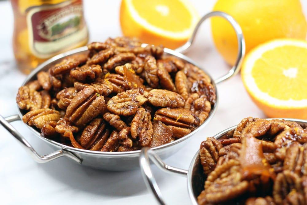 two metal bowls with handles filled with orange glazed pecans