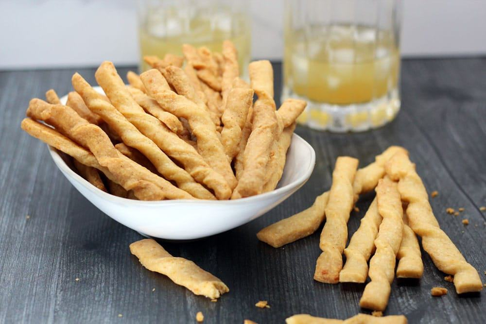 a white bowl filled with twisted baked cheese straws on a wooden surface