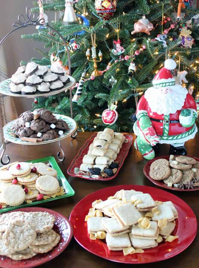 an array of various cookies on platters in front of a Christmas tree