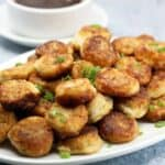 a white platter topped with a pile of browned discs of potato sprinkled with chopped scallions
