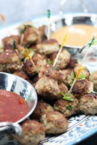 Pork and Mushroom Meatballs piled on a platter with bowls of orange and red sauces