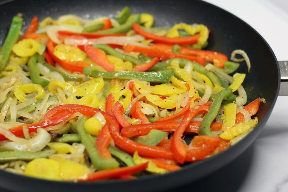 sliced red, green, and yellow peppers with sliced onions sauteing in a black skillet