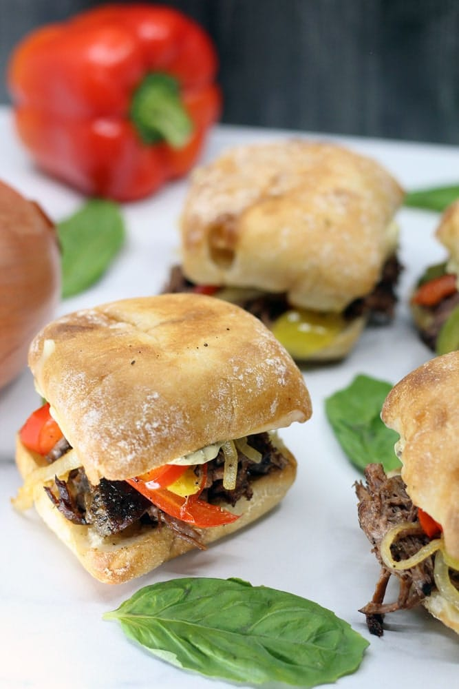 four Crock-Pot Italian Beef Sandwiches on a white platter garnished with whole basil leaves