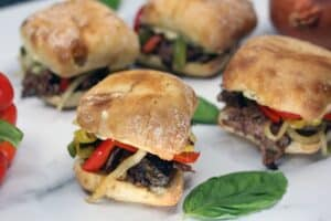 beef sandwiches topped with cooked sliced vegetables on browned buns