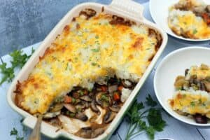 Vegetarian Shepherd's Pie with a big scoop taken out of the corner to expose the filling inside with mushrooms, peas and carrots with two individual servings in small bowls