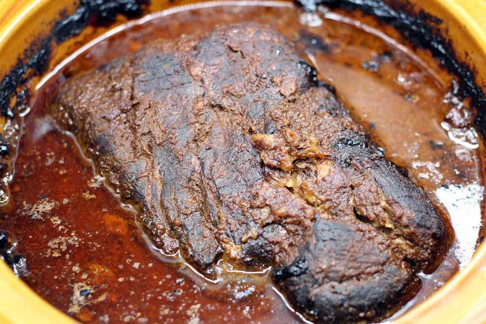 cooked blackened pork butt in the crock pot surrounded my cooking juice and mole after hours of cooking