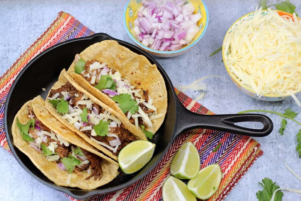 3 Crock-Pot Mole Pork Tacos in a small cast iron skills garnished with lime wedges and small bowls of diced red onion and shredded cheese on the side
