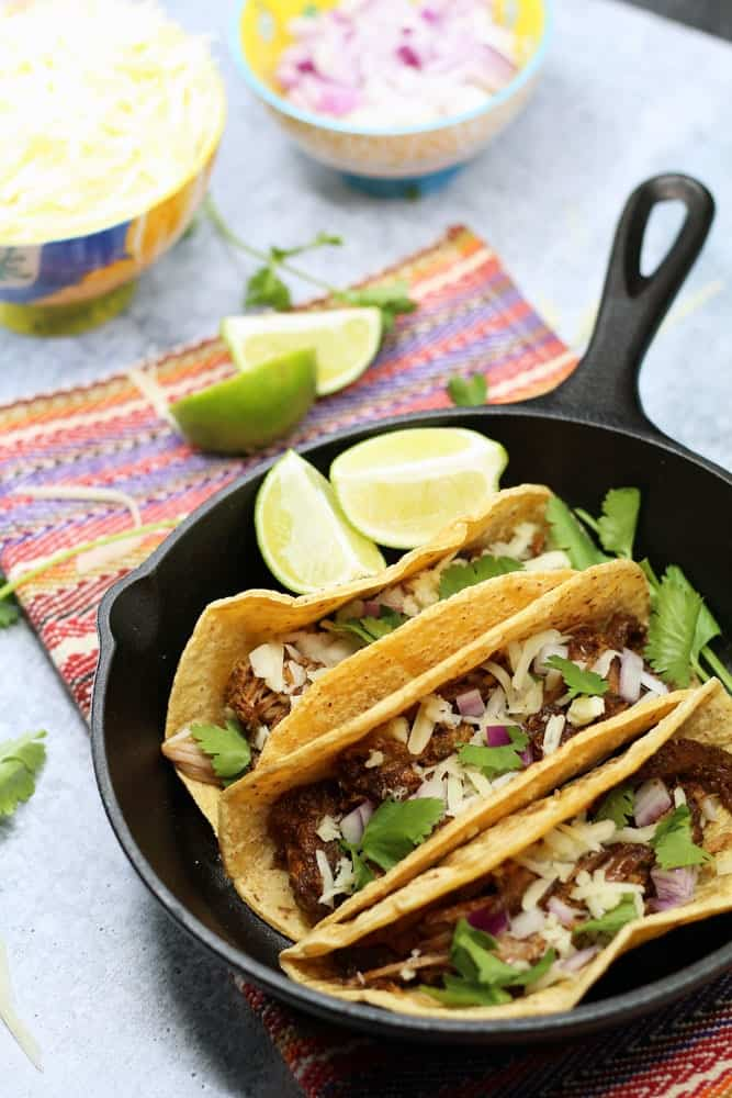 3 tacos in a small cast iron skills garnished with lime wedges