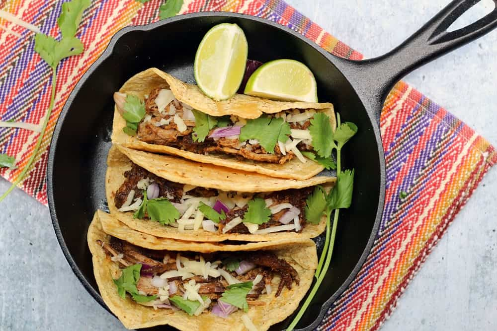 3 Crock-Pot Mole Pork Tacos in a small cast iron skills garnished with lime wedges