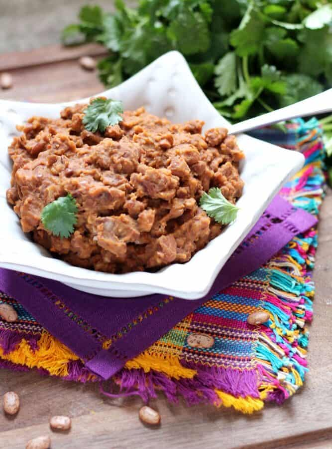 Refried Beans with Chorizo garnished with cilantro leaves in a star shaped white bowl sitting on colorful Mexican-style linens with a cilantro bunch in the background