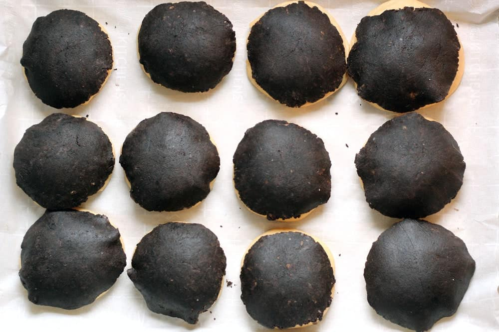 concha dough balls after topping with the chocolate dough sitting on a sheet pan lined with parchment paper