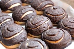 freshly baked rows of chocolate conchas on a baking sheet lined with parchment paper