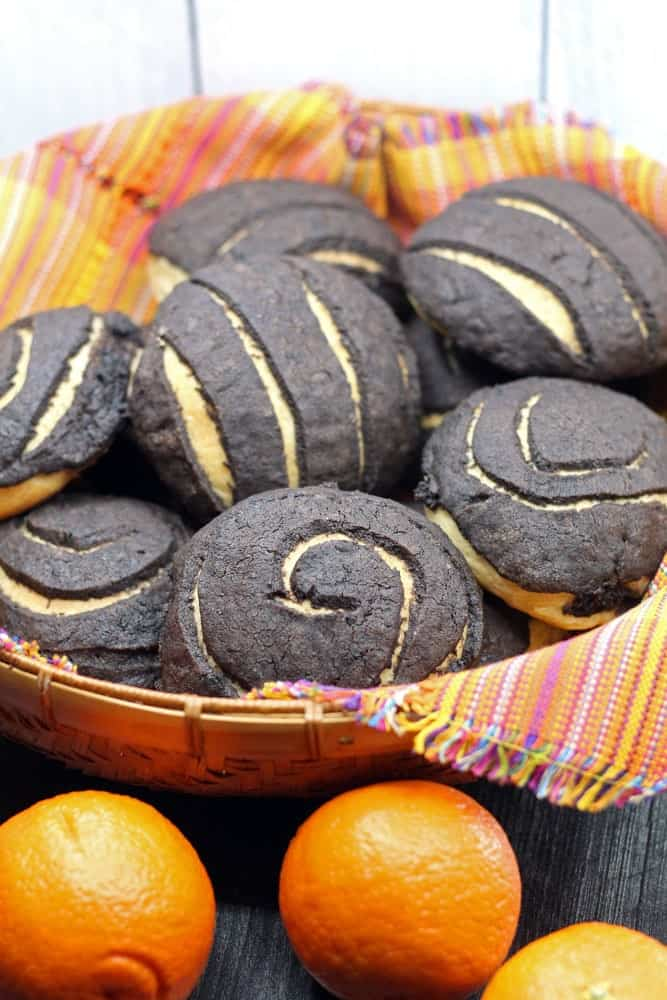 Chocolate Conchas or Mexican Sweet Bread flavored with chocolate and orange in a woven basket lined with a colorful Mexican style linen and surrounded by fresh oranges