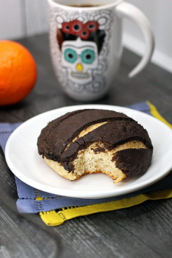 a Chocolate Concha or Mexican Sweet Bread flavored with chocolate and orange on a white plate with a bite taken out of it and a cup of coffee in the background in a day of the dead coffee mug