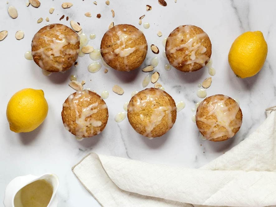 Citrus Almond Muffins evenly spaced on a white marble background with a side of glaze and sprinkled with sliced almonds